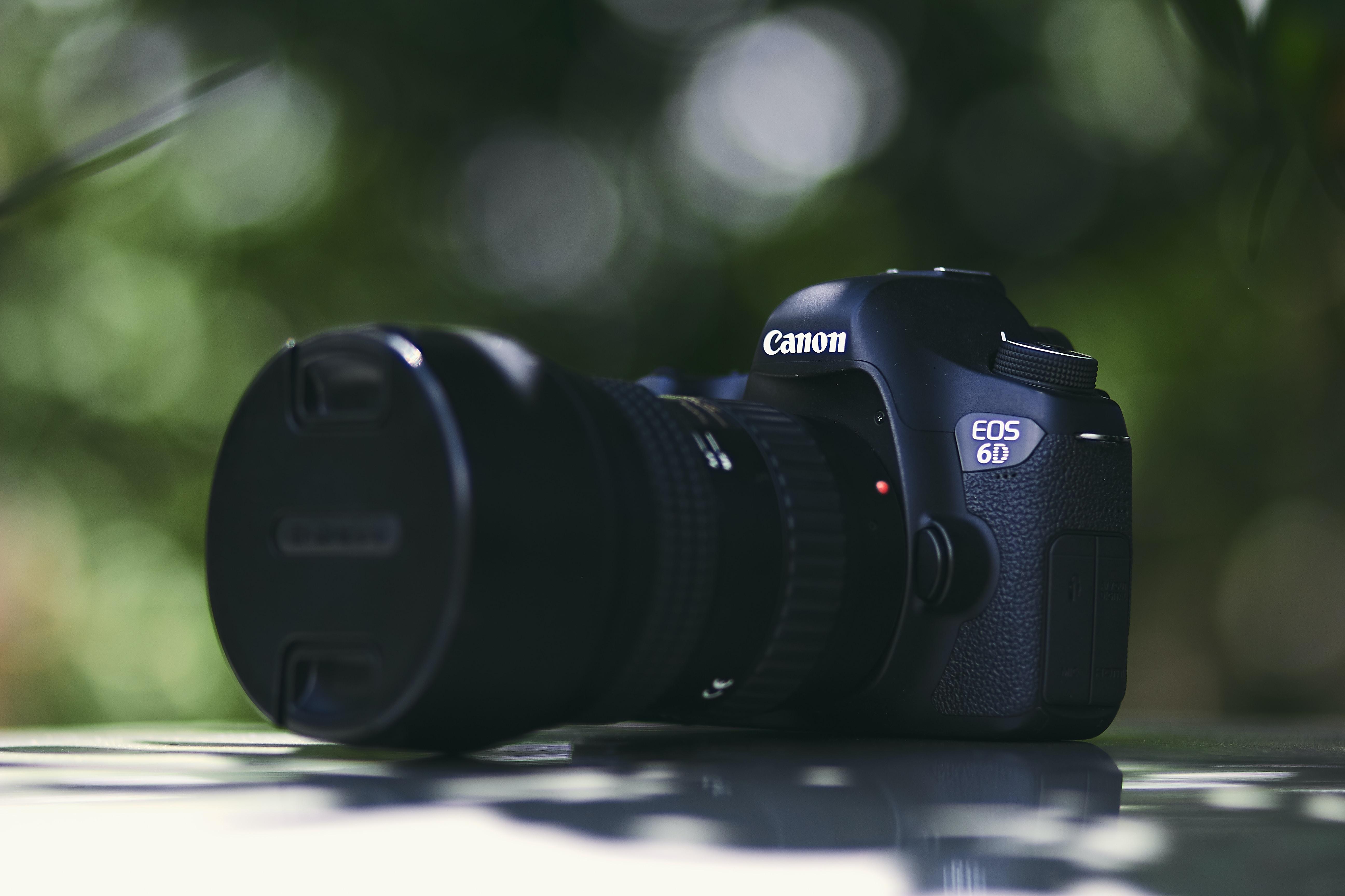 black Canon EOS 6D DSLR camera on white surface
