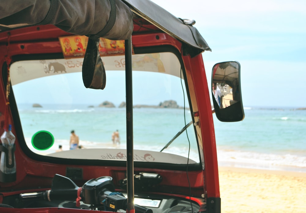 photo of red auto-rickshaw facing sea