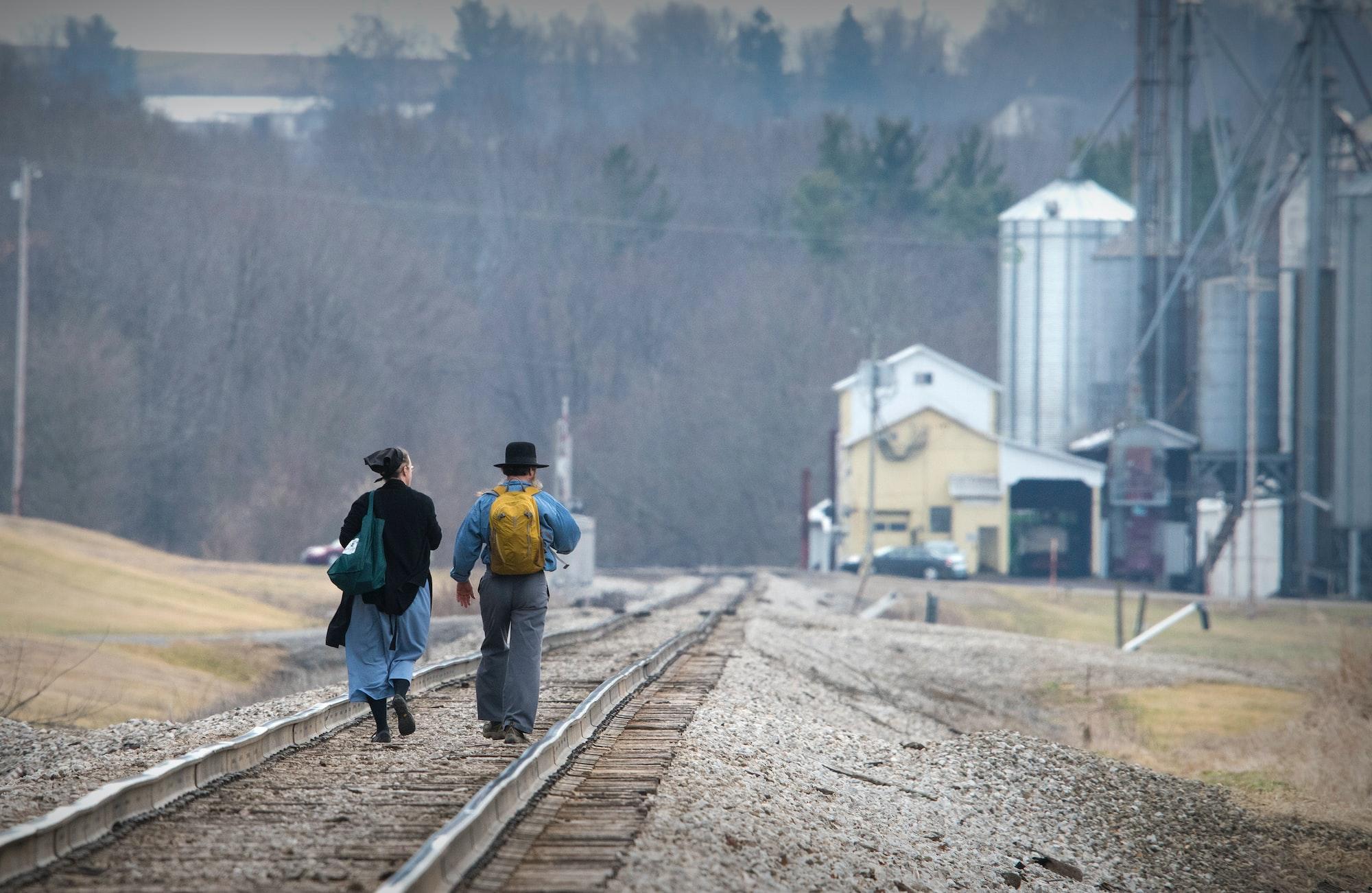 Amish couple walking railroad tracks
