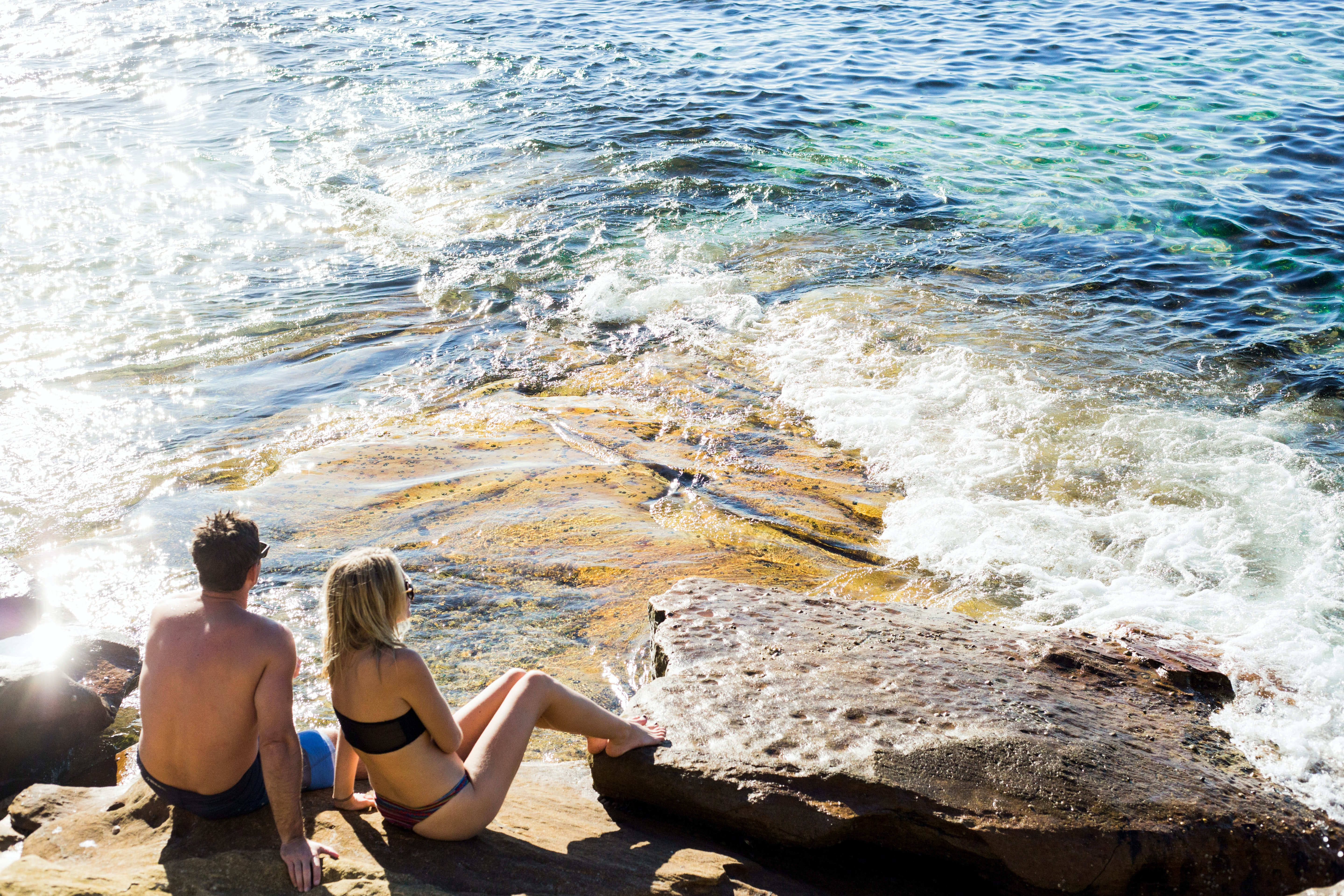 man and woman sitting next to each other in beach