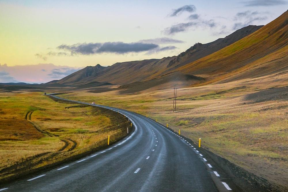 empty roadway between grass field during daytime
