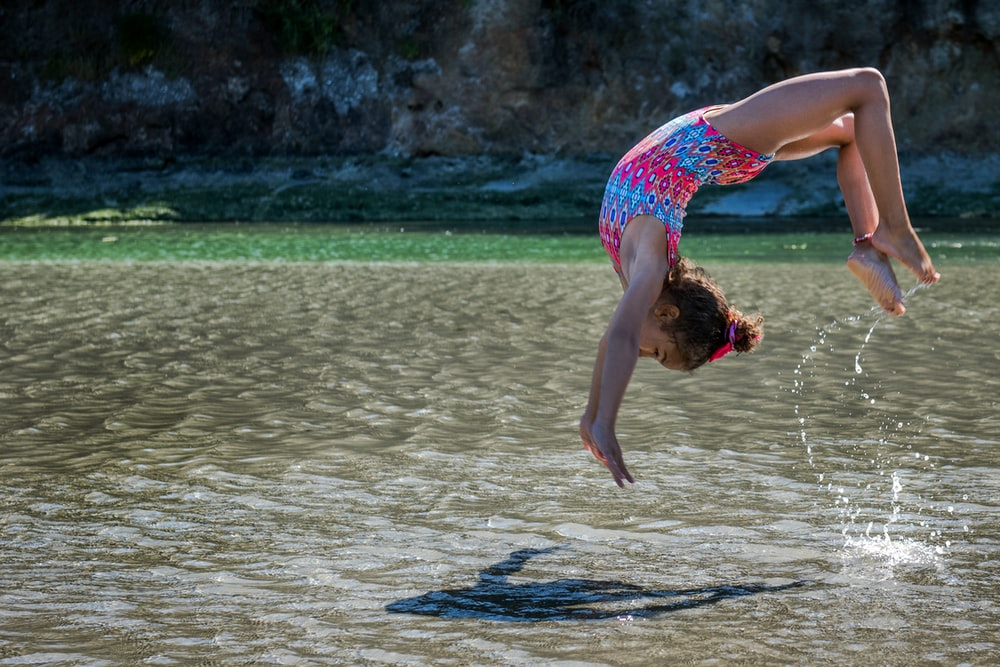 girl diving in body of water at daytime