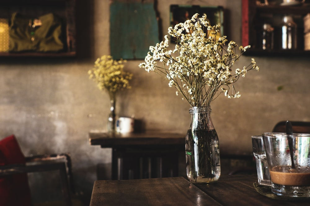 white petaled flowers with clear glass vase on brown table