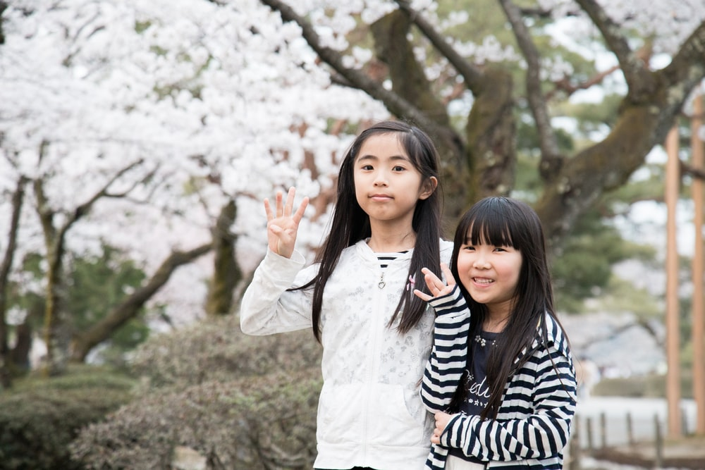 two girls standing behind brown tree with white leaves