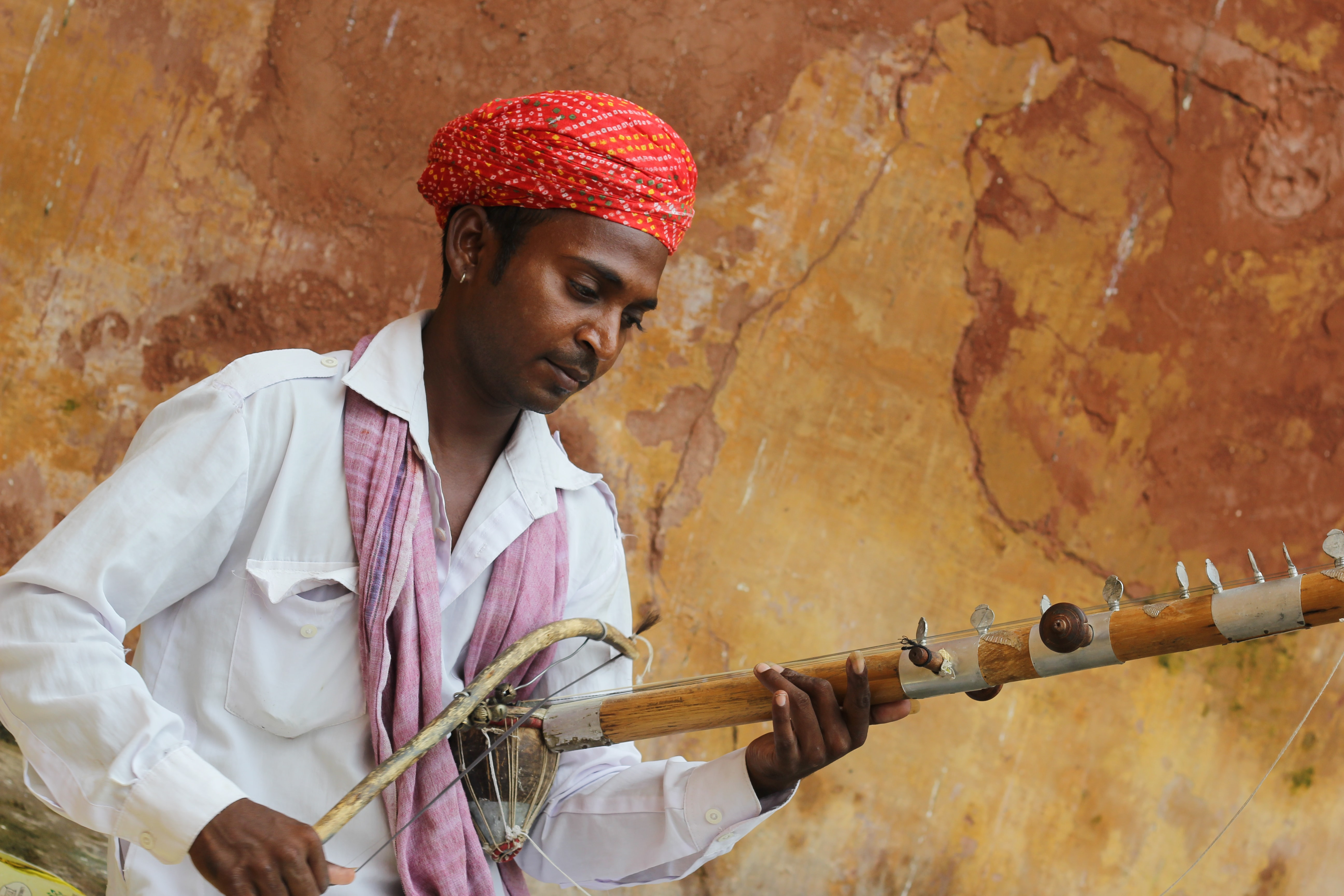 man in red turban playing musical instrument