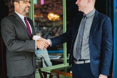 初対面で握手をするスーツを着た男性2人