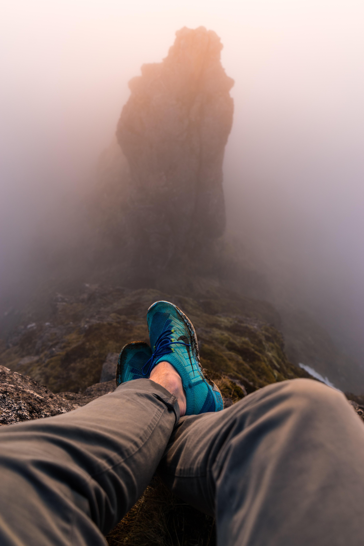 person sitting on mountain edge