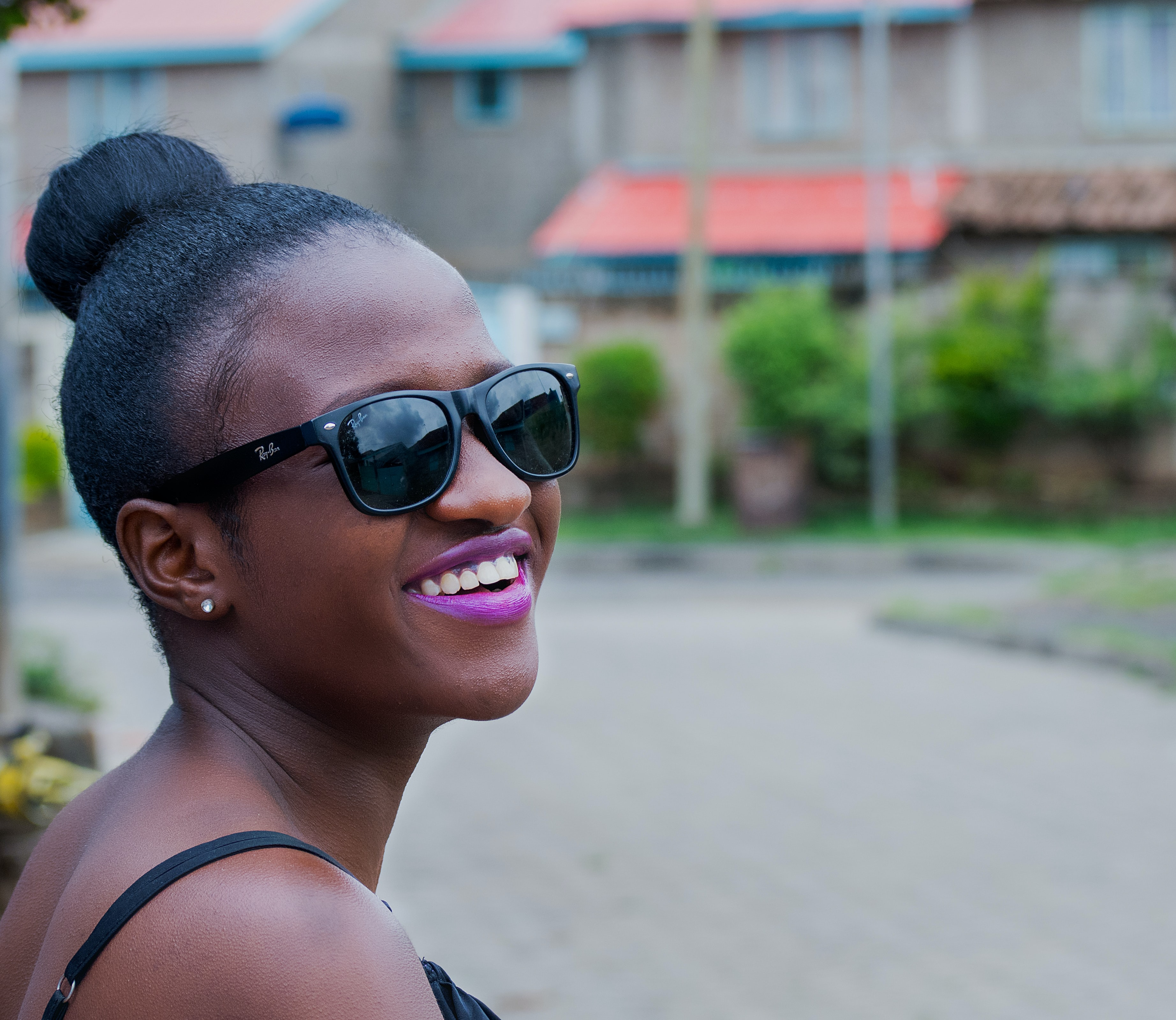 woman wearing black Ray-Ban Wayfarer-style sunglasses smiling