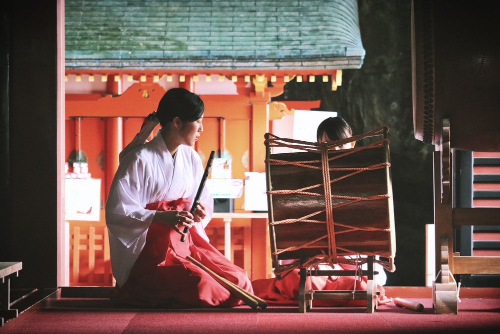 woman playing bamboo wind instrument in front of percussion instrument