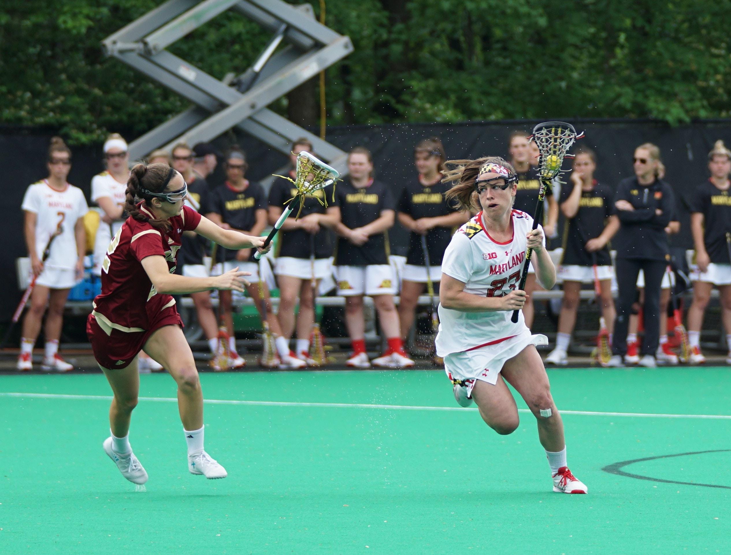 women playing lacrosse game during daytime