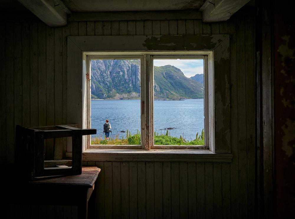 person standing near sea window view