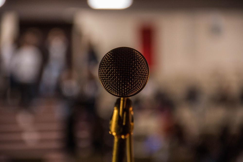 selective focus photography of brass-colored microphone