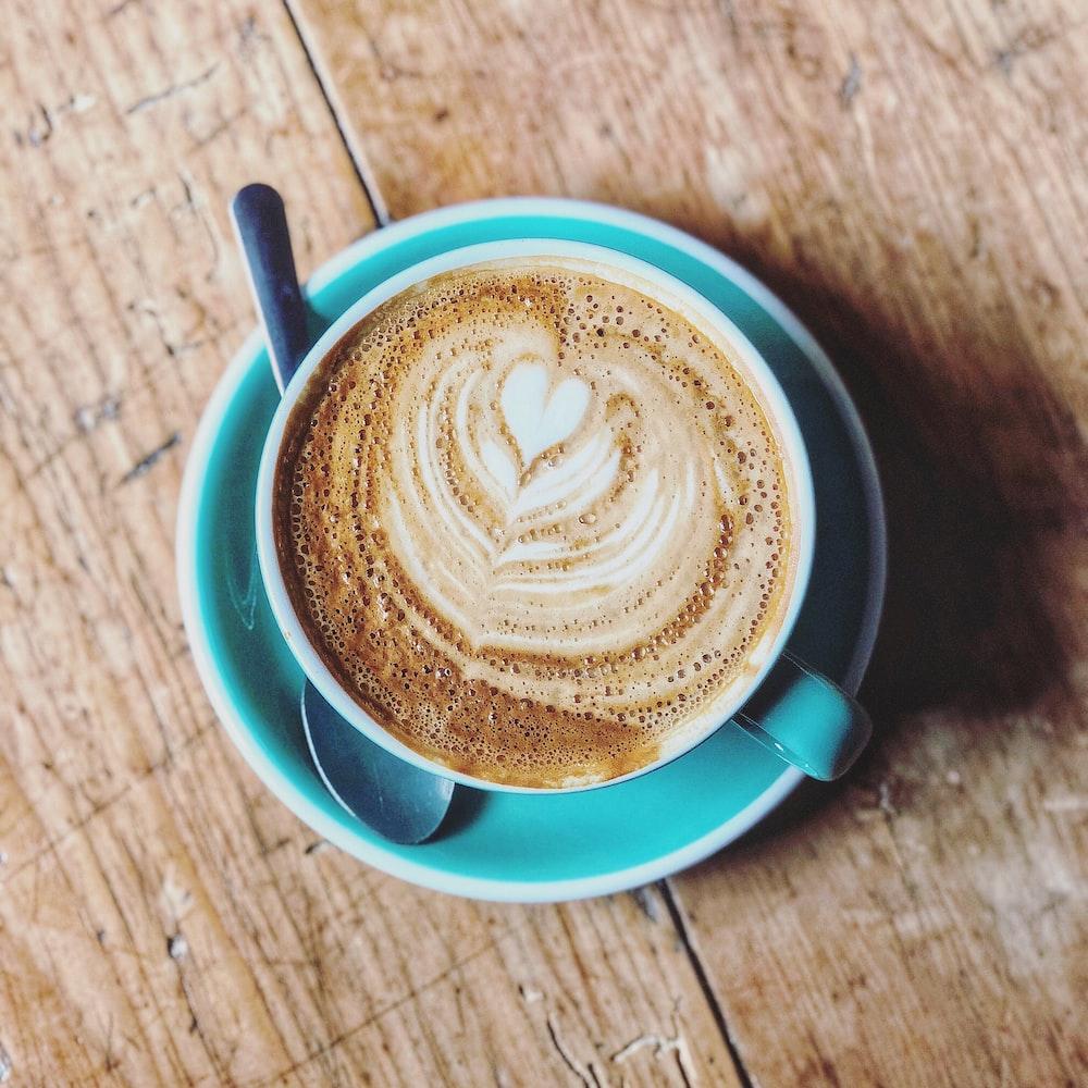 latte filled blue ceramic cup on saucer