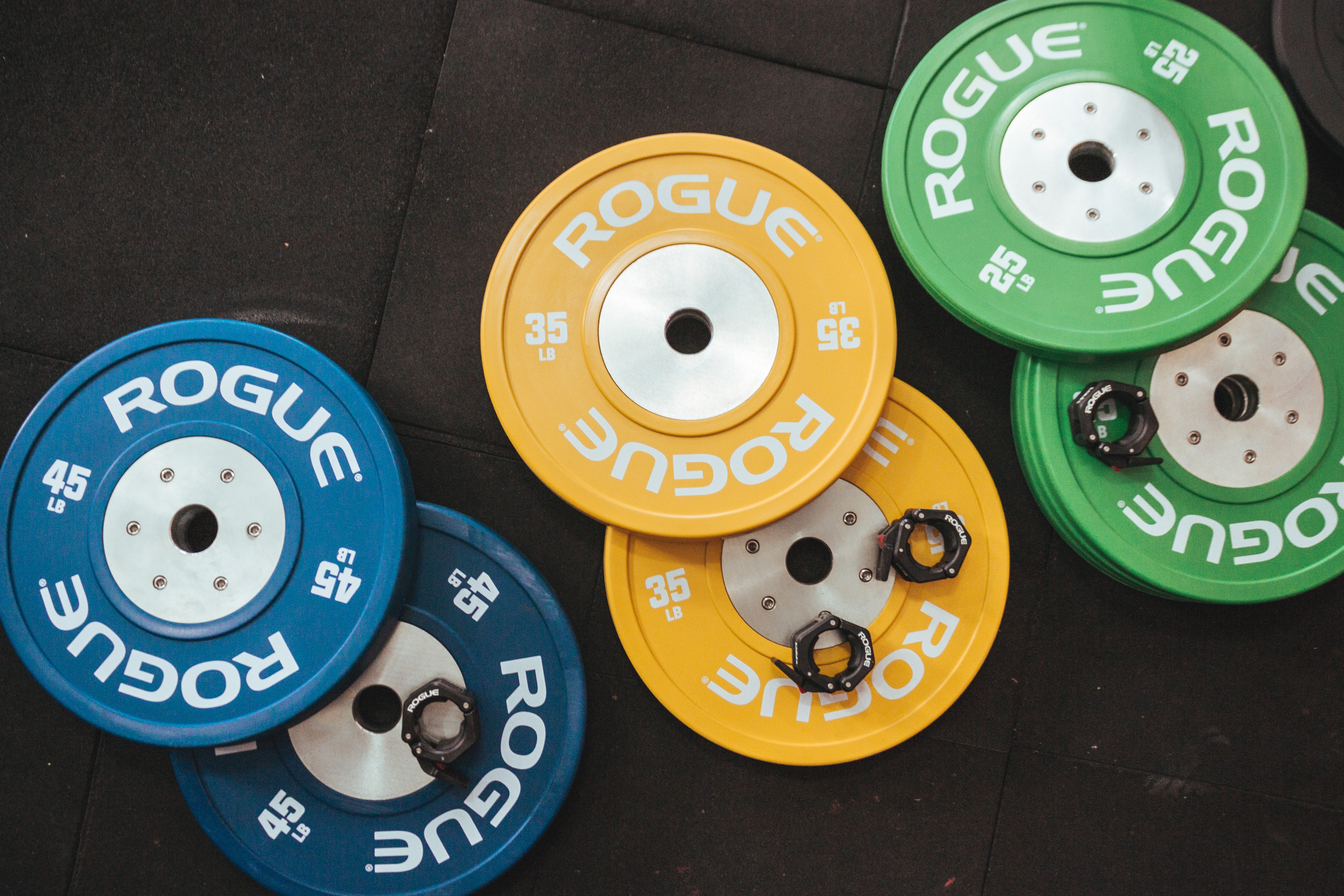 three pairs of assorted-color Rogue bumper plates