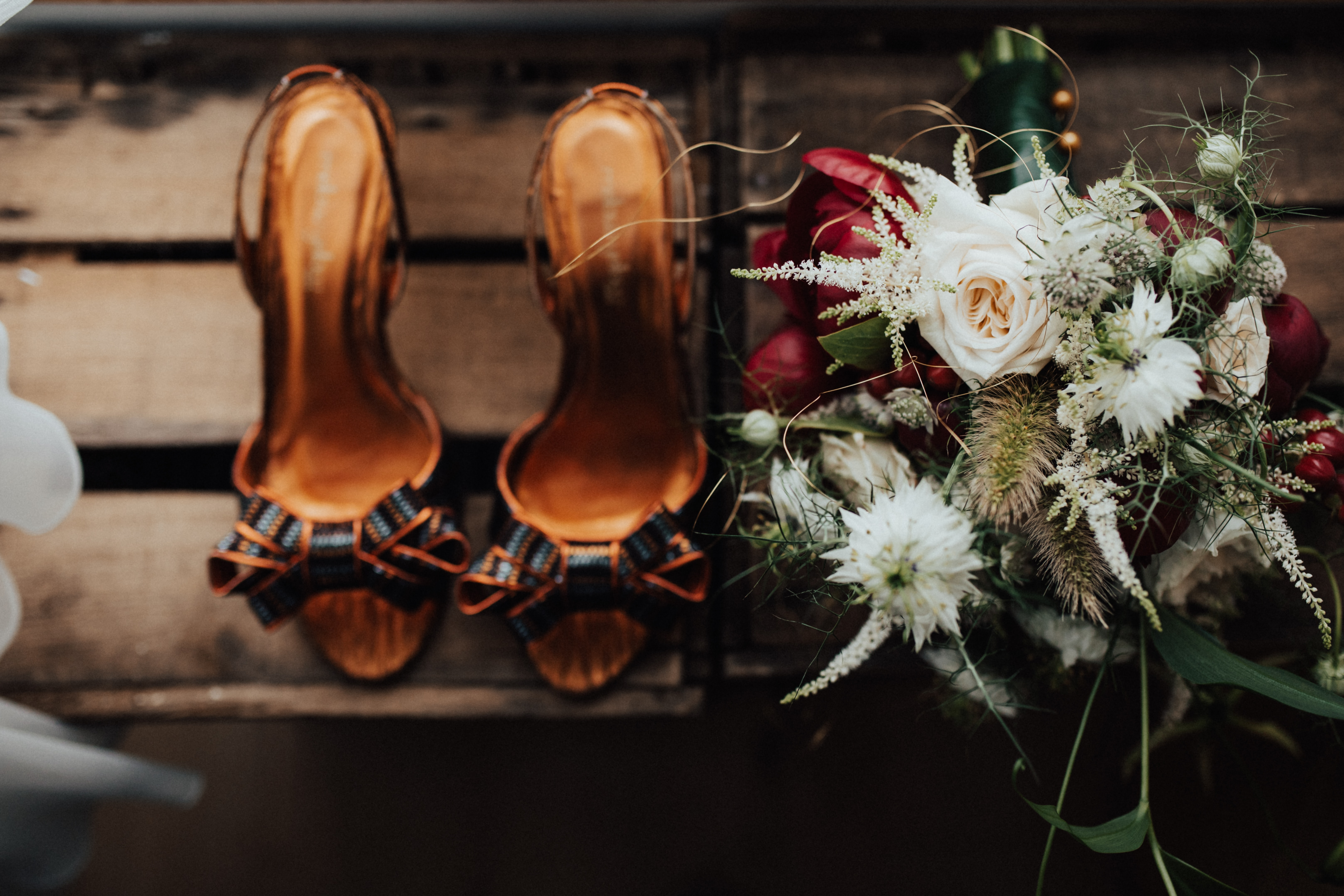 pair of brown heels near white petaled flowers