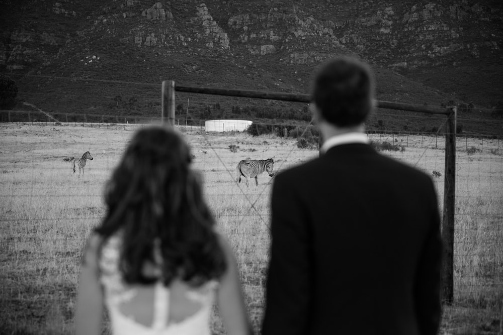 grayscale photography of man and woman in front of zebra