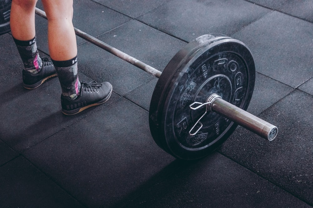 person standing in front of gray and black barbell