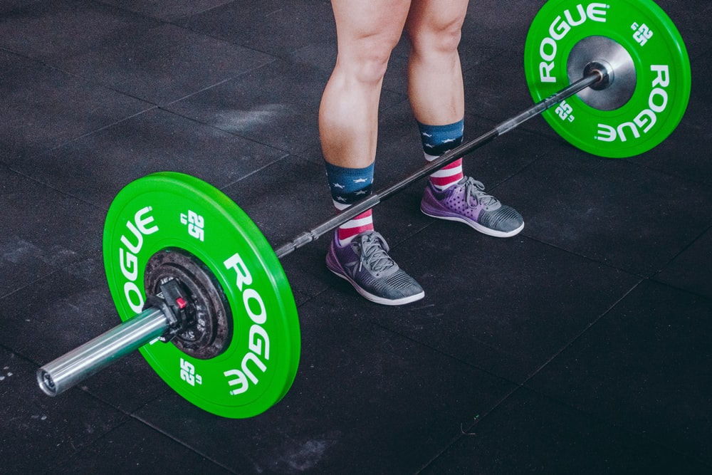 person standing in front of gray and green barbell
