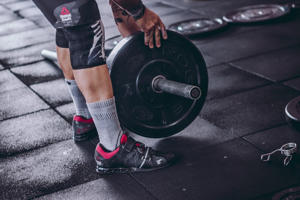 person holding black barbell plate