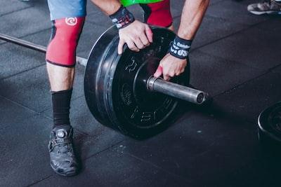 バーベルの重量を変えている人の画像