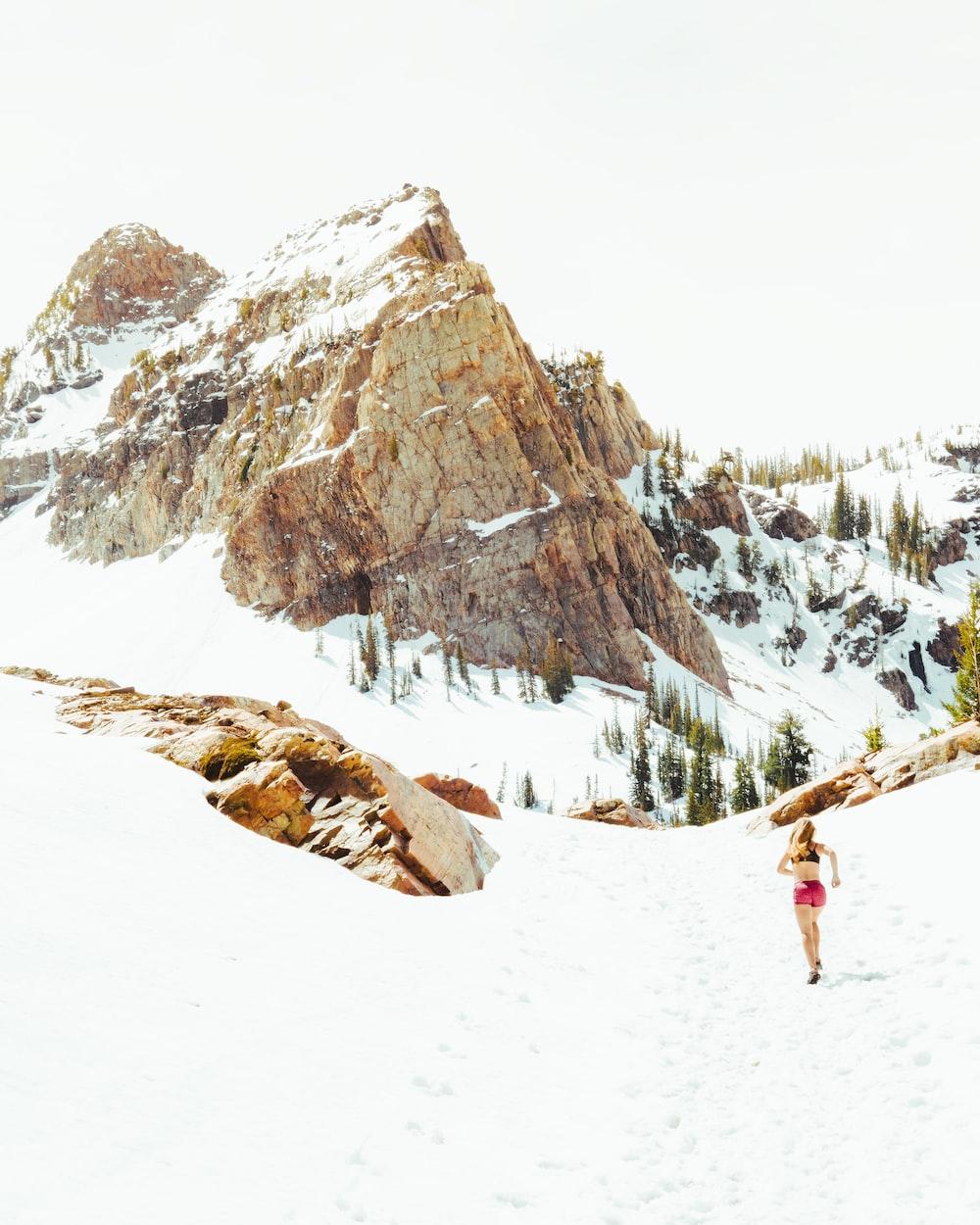 woman in pink shorts running through mountain