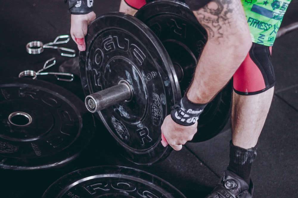 man holding black Rogue weight plate