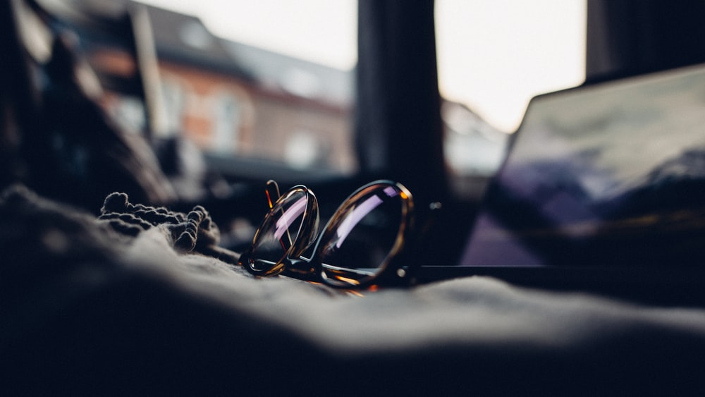 shallow focus photography of black sunglasses with brown frames