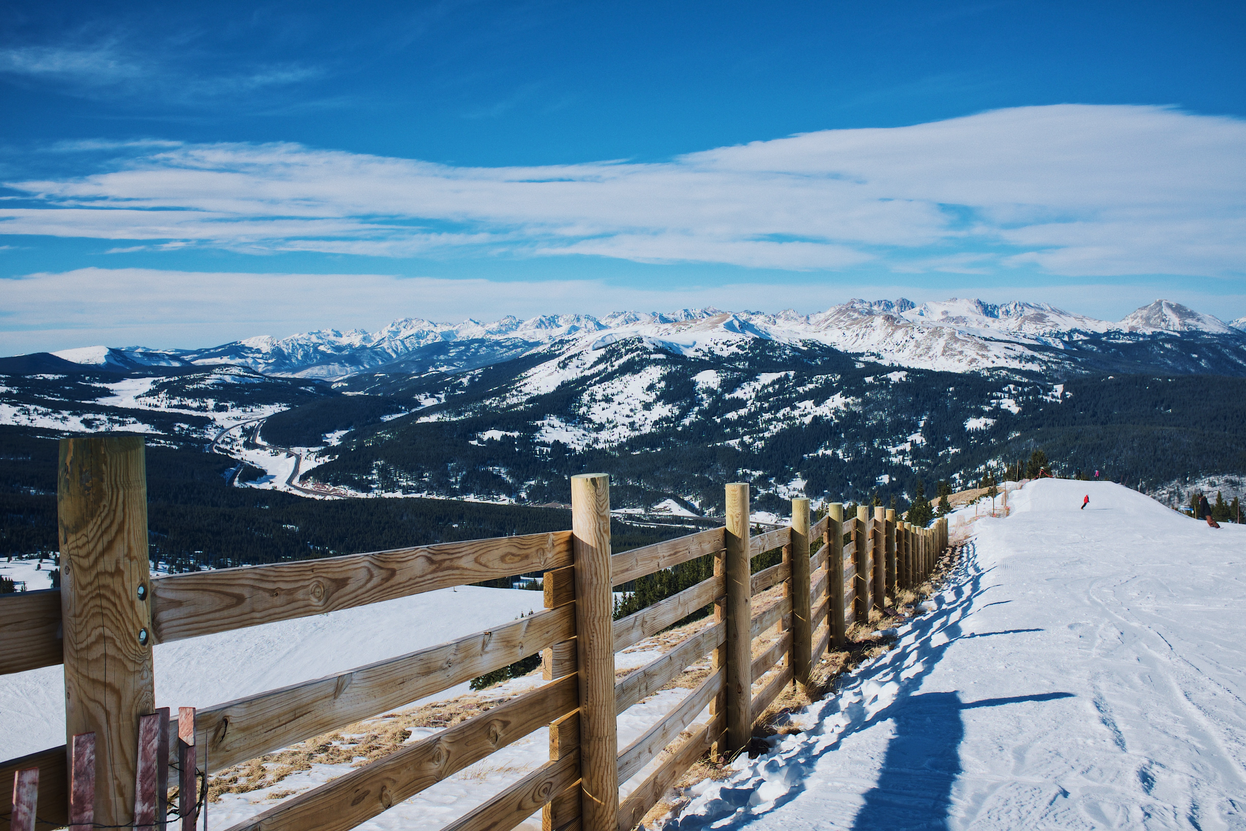 snowfield and brown wooden fence near mountain at daytime