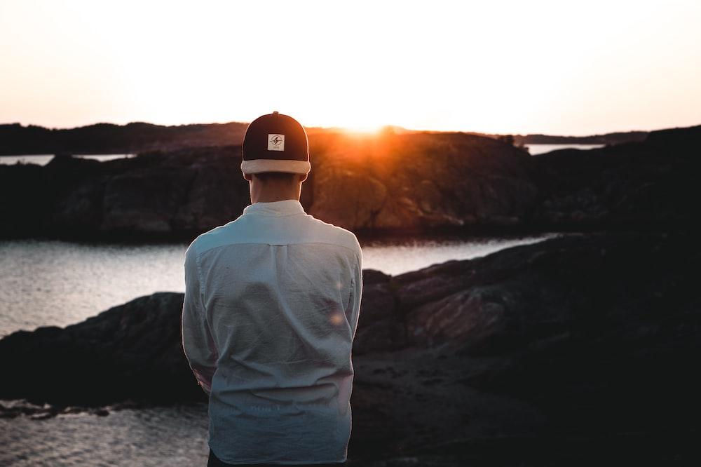 man wearing cap backwards facing the sea