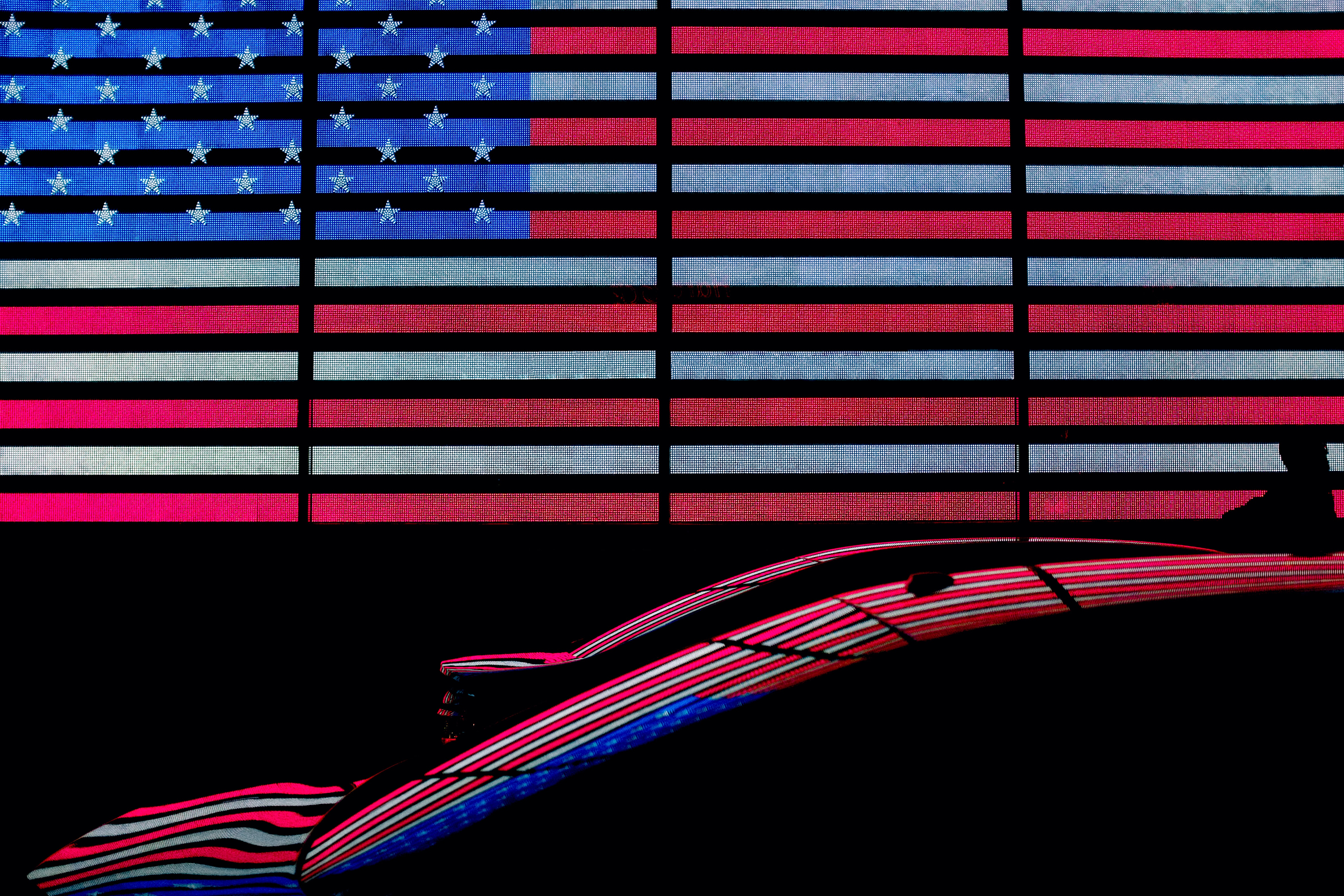 two cars in front of American flag