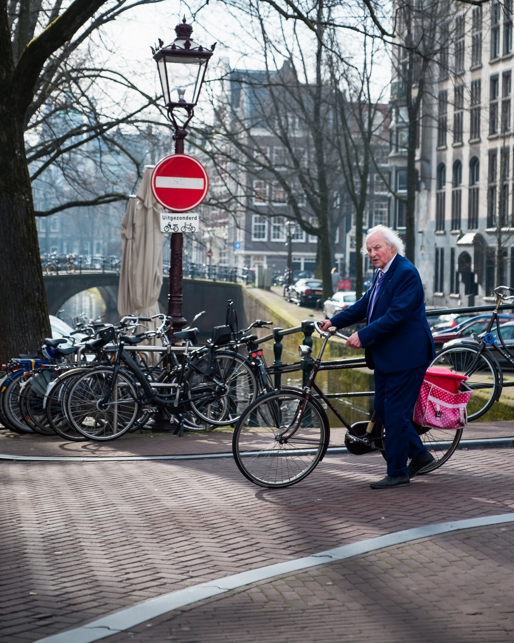 man wearing black notched lapel suit jacket holding bike