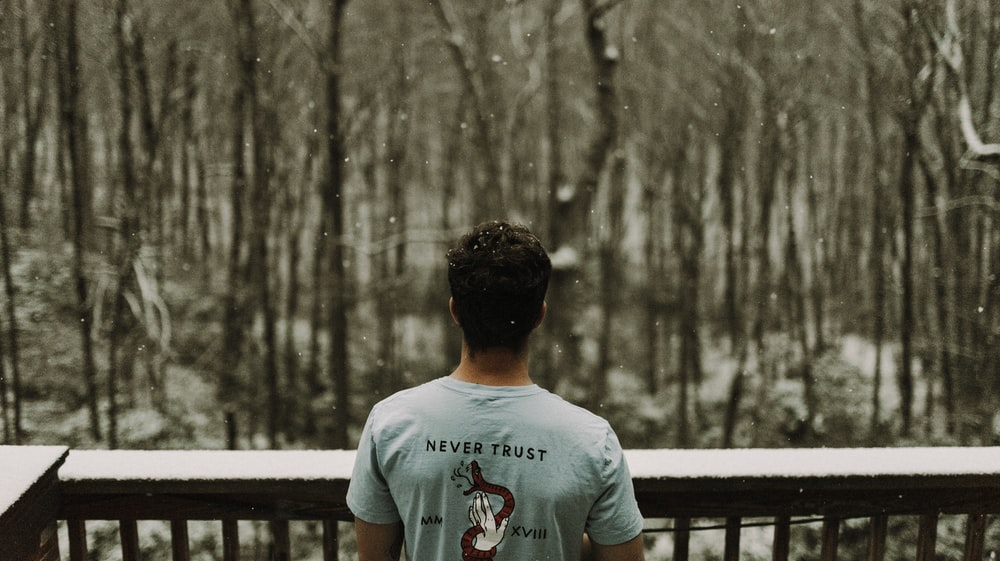 man wearing gray T-shirt standing beside brown wooden railing during snowy day