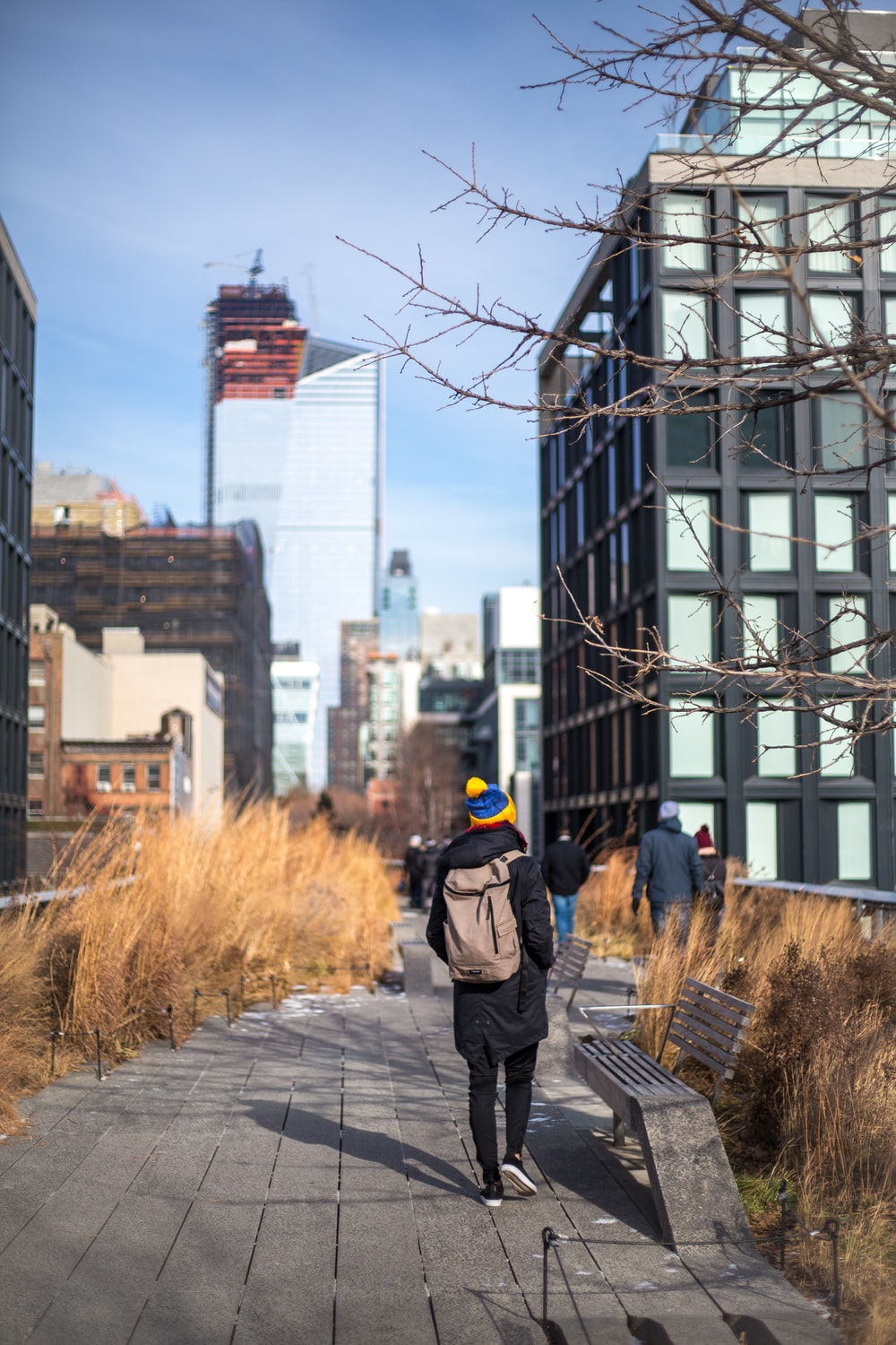 person wearing winter clothes with brown backpack walking on gray pathway outdoors during day