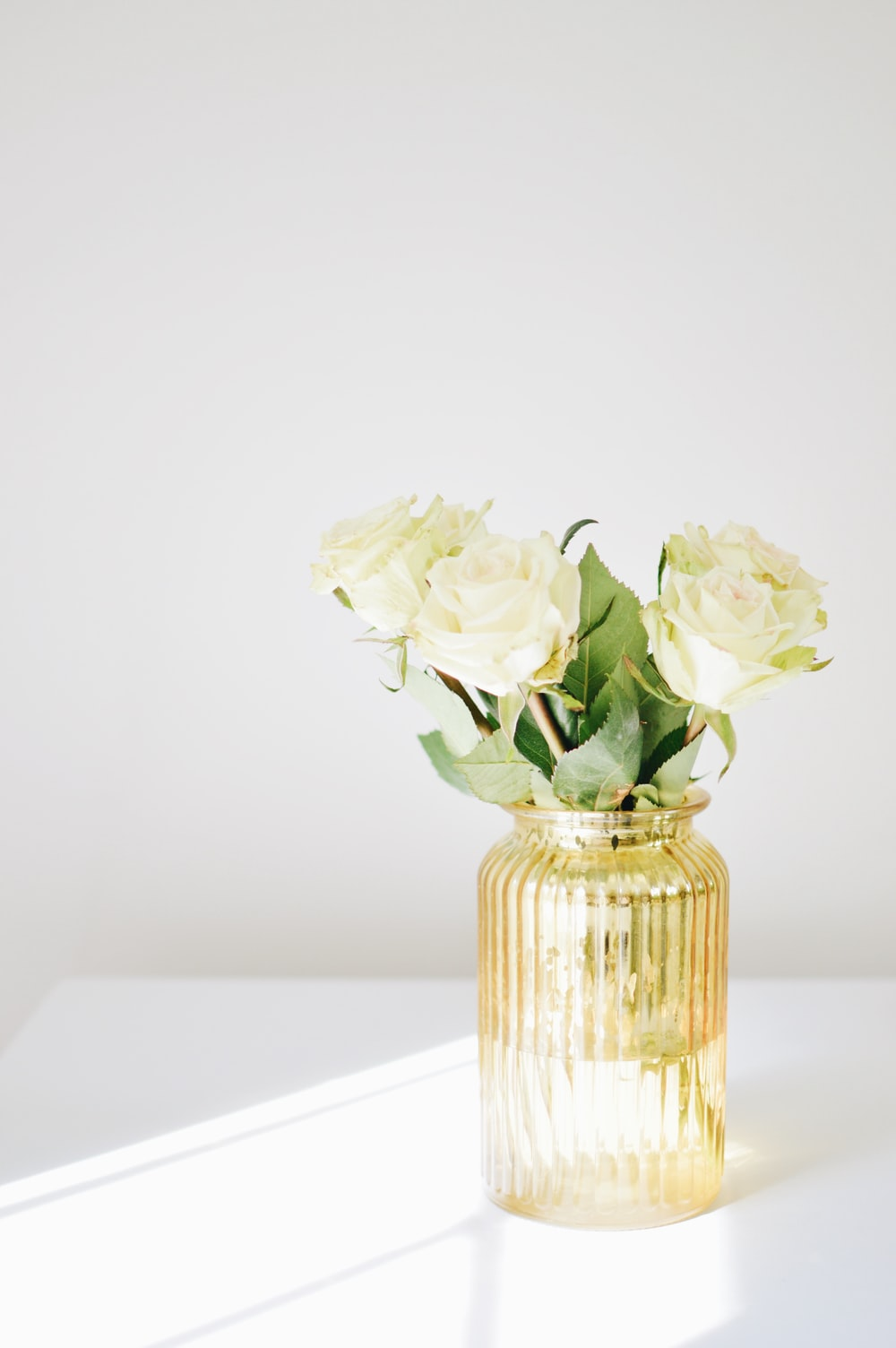 white rose centerpiece on white wooden table