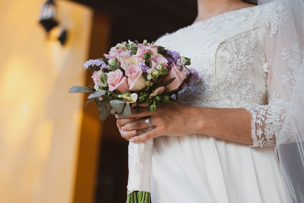 bride holding pink bouquet of rose