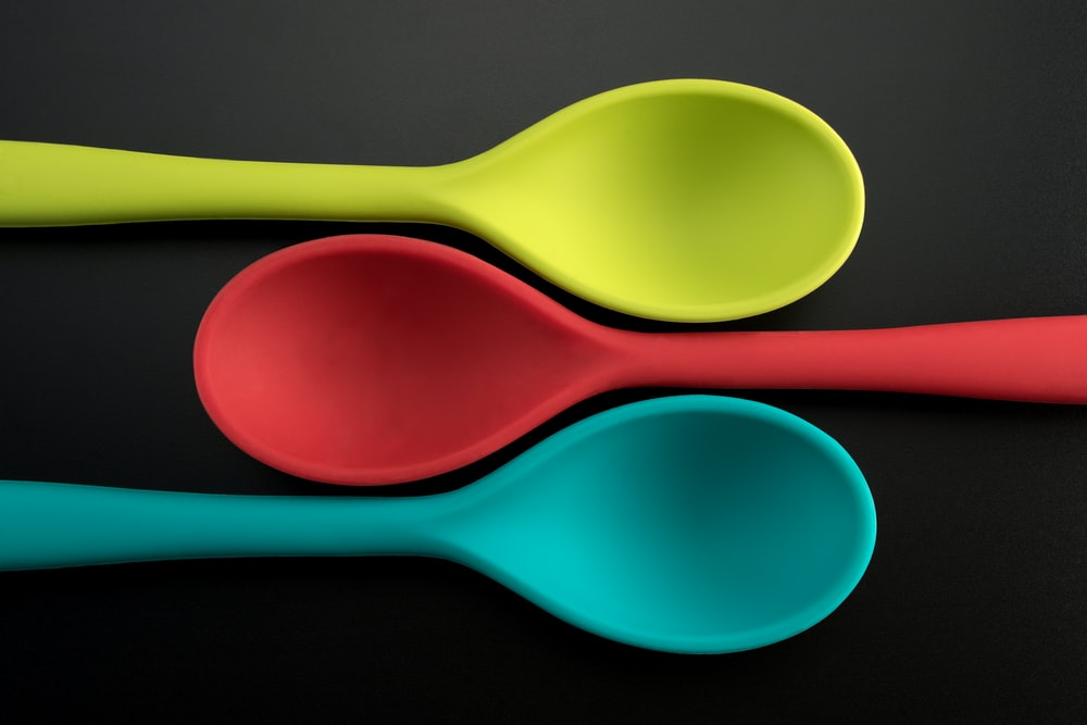 three green, red, and blue plastic spoons