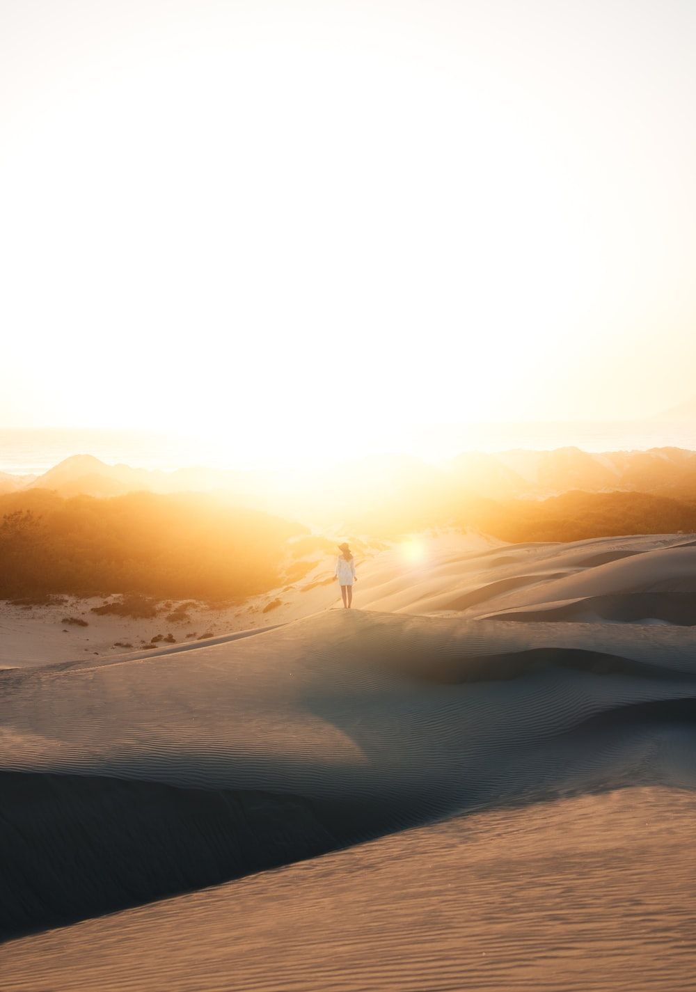 woman in white dress standing on sand photo during sunset