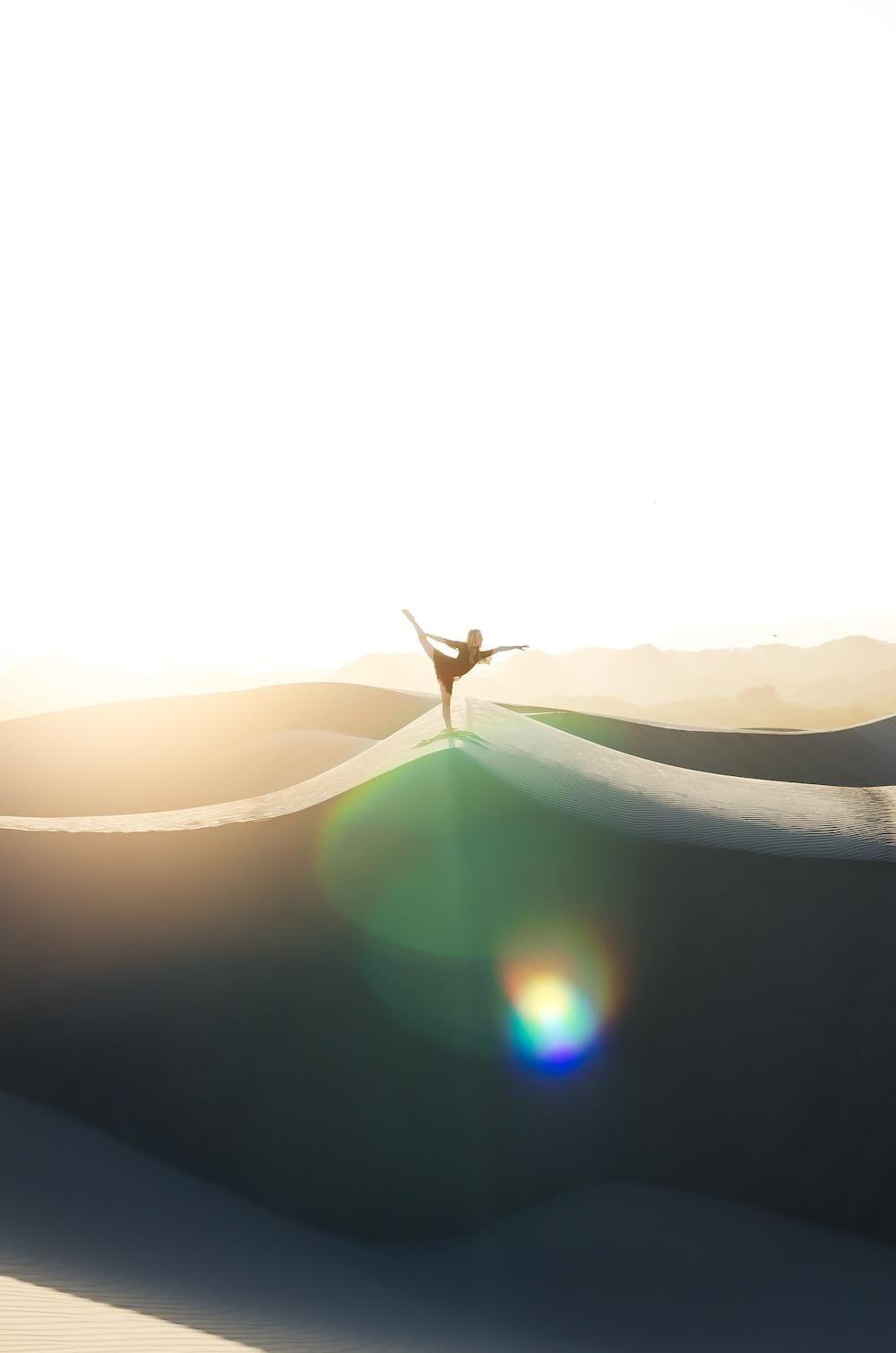 woman doing ballerina pose on sand dune
