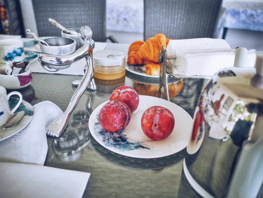 three red apple fruits on white ceramic plate