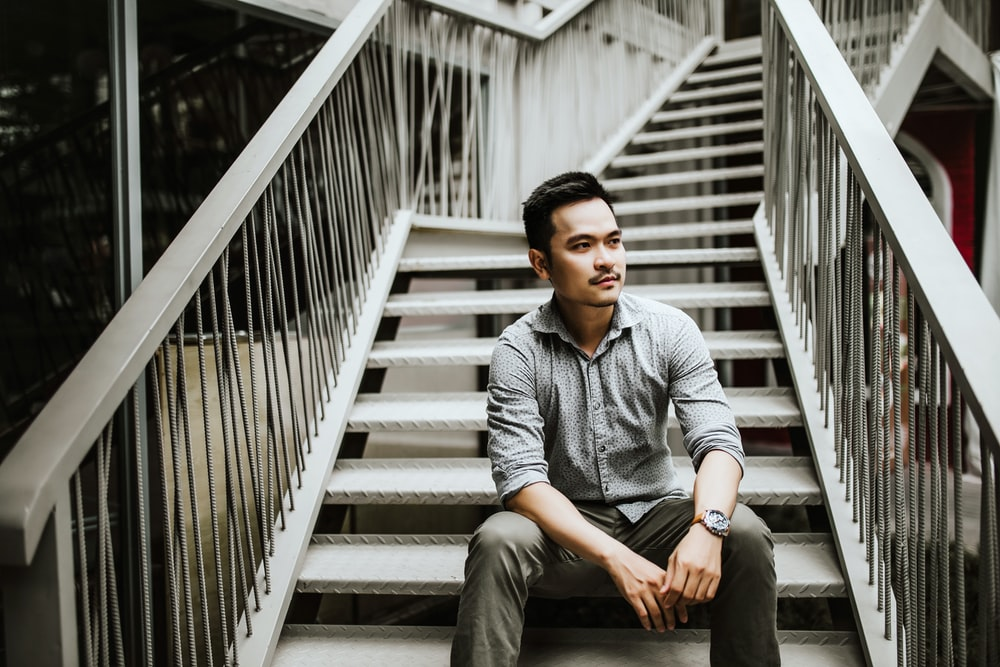 man sitting on stairs during daytime