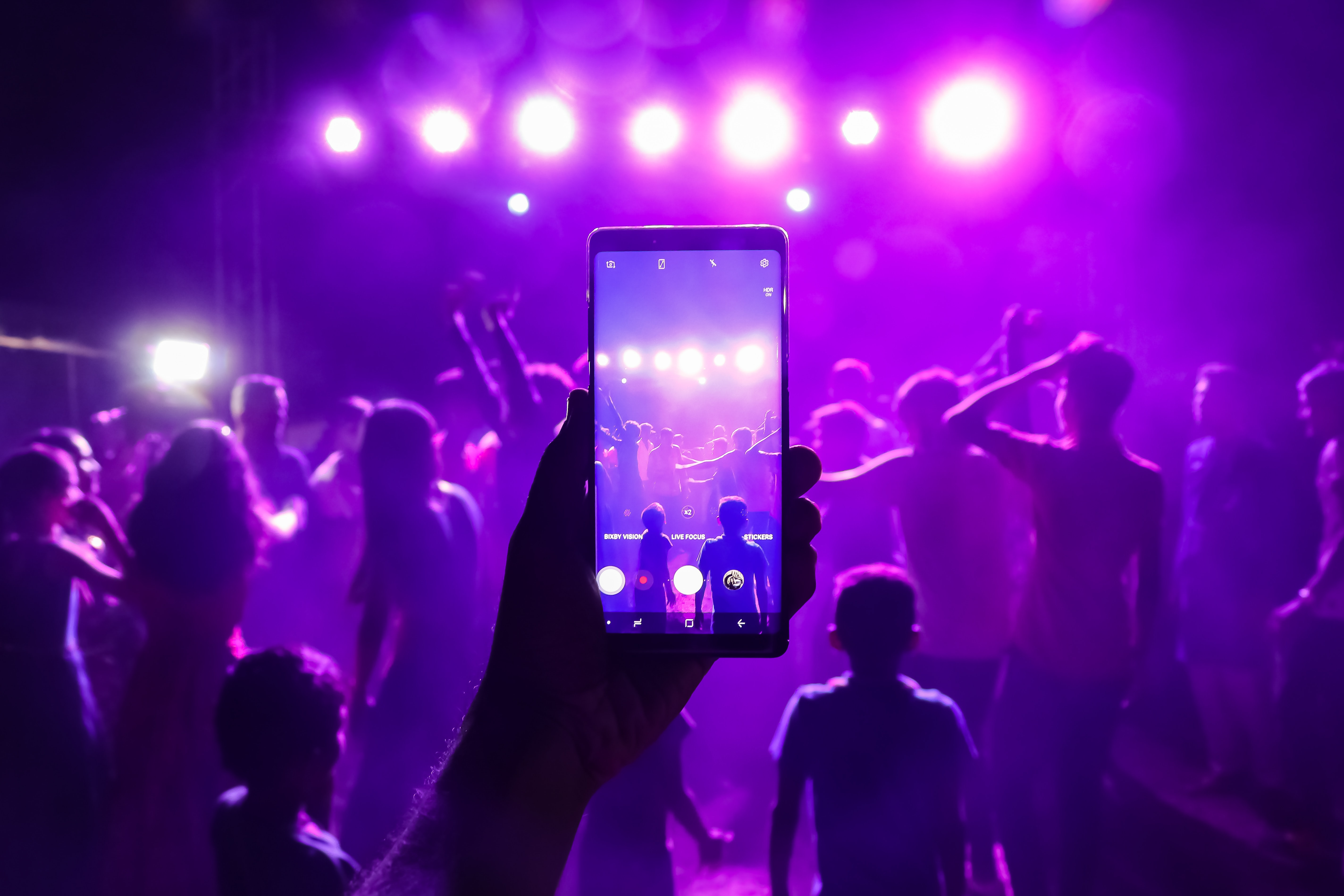person holding smartphone taking photos inside bar