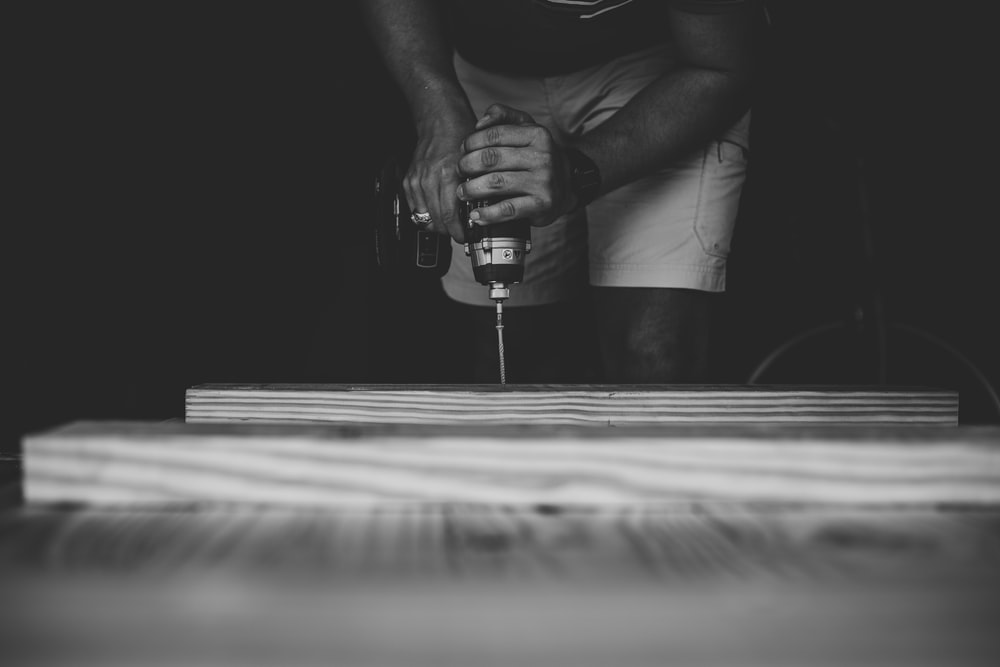 person drilling brown wooden board using power drill