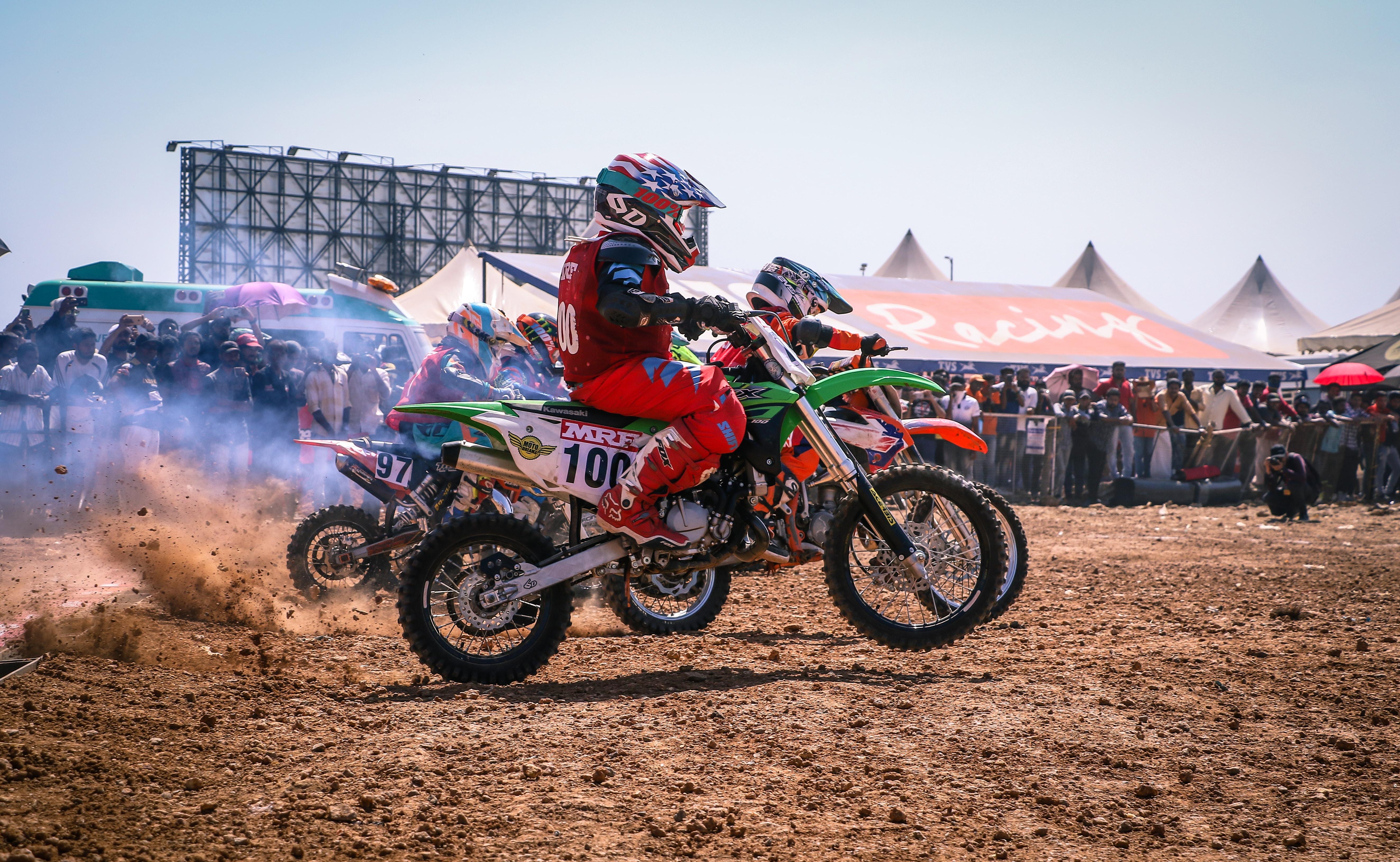 motocross dirt bike racing with people watching beside on focus photo