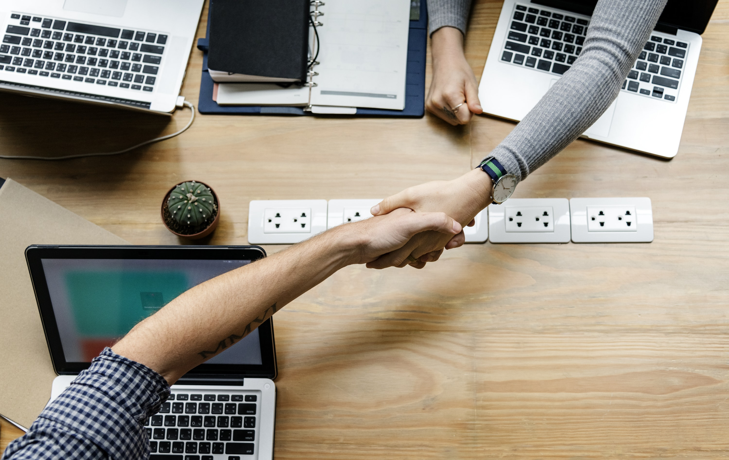 two person handshaking in front of MacBook Pro