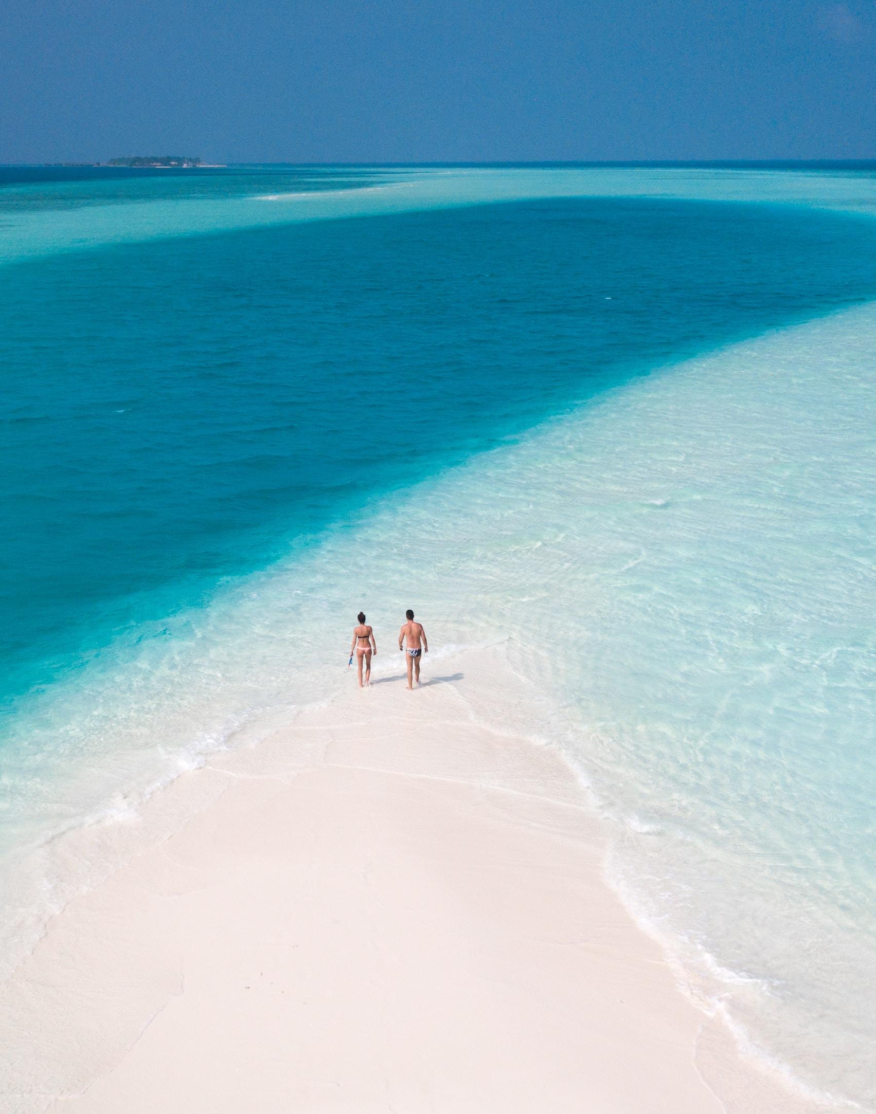 man and woman walking on seashore during daytime