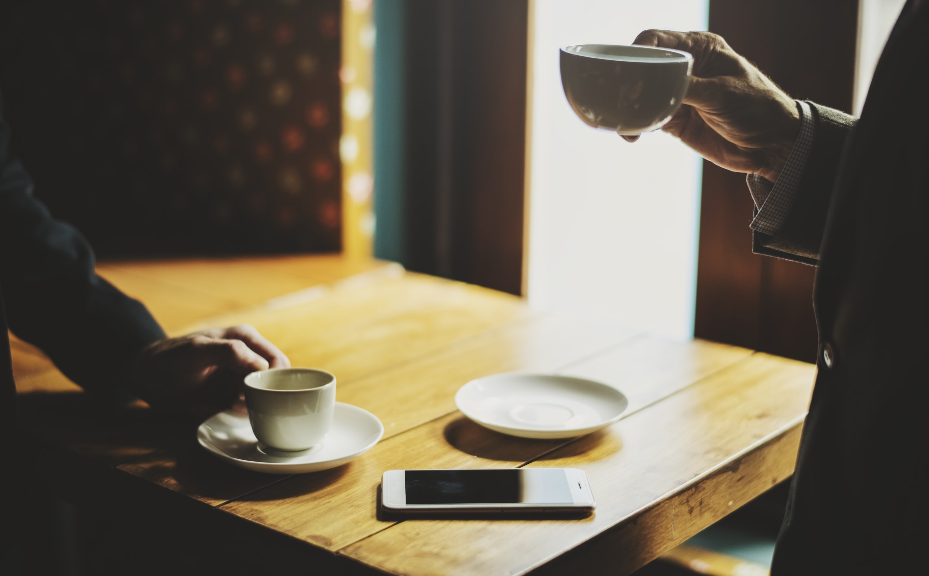 person holding white ceramic cup infront of person near the brown wooden table