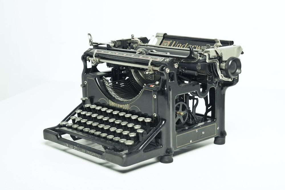 black and gray typewriter on white table