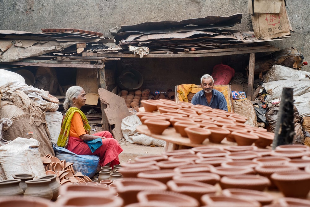 two person sitting near clay pots
