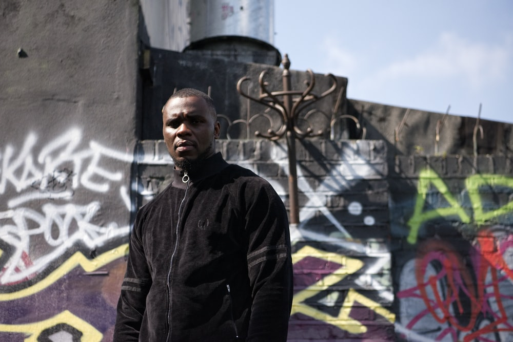 man near wall with graffiti