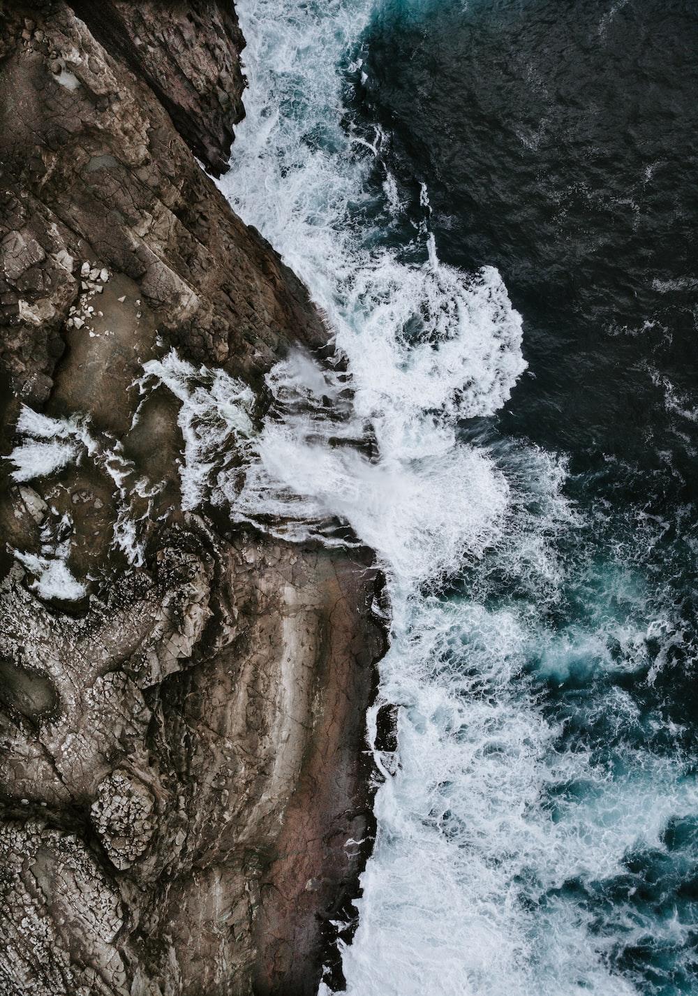 bird's eye view water waves crashing to rocks